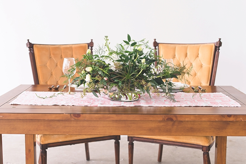 Unique wedding table setting with green compote centerpiece on a handmade coral table runner and wooden table