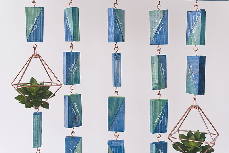 Patterned blue and green hanging seating chart with colored wood blocks and copper hooks
