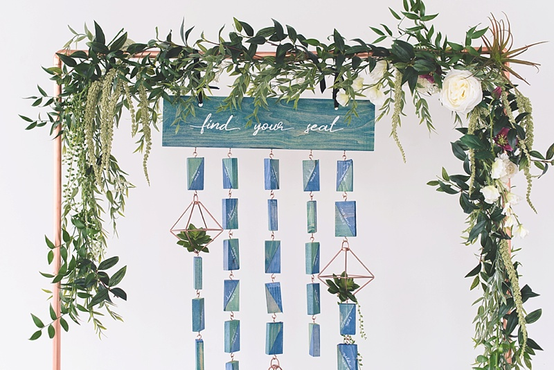 Unique hanging wood wedding seating chart on a copper stand