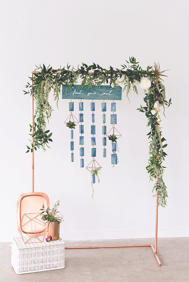 Unique tall wedding seating chart on a modern copper display stand and textured flowers and greenery