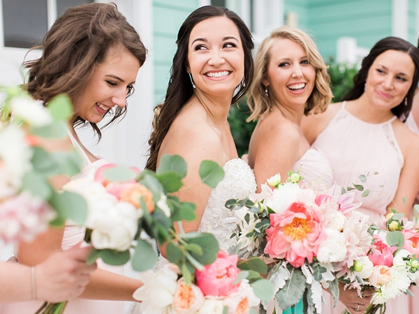 Happy bride and bridesmaid with peach coral bouquets