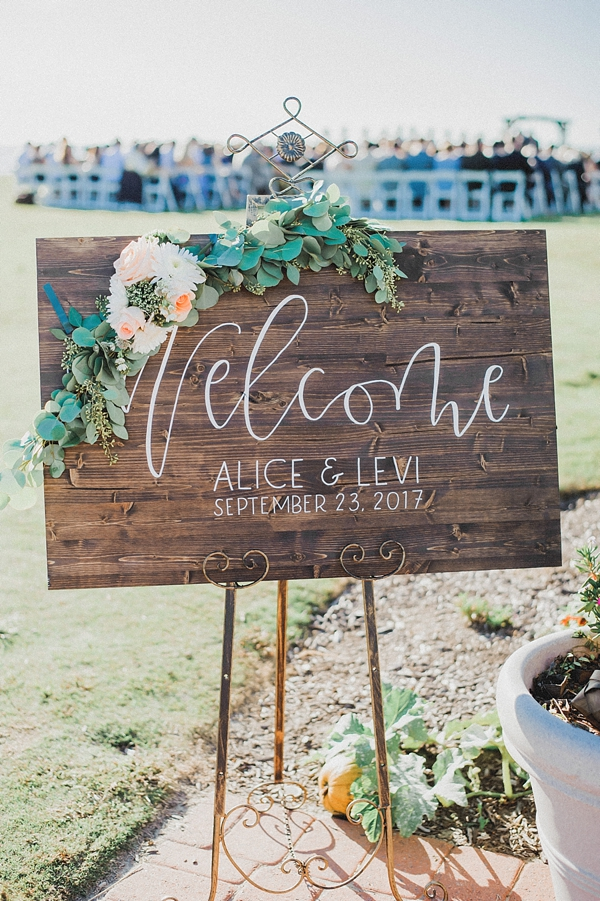 Wooden welcome sign with calligraphy and floral swag for outdoor wedding ceremony