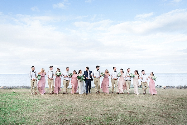 Wedding party with blush dresses and navy blue bow ties