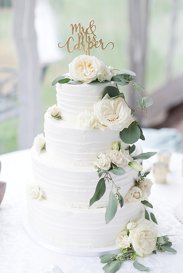 Simple textured white wedding cake with personalized cake topper