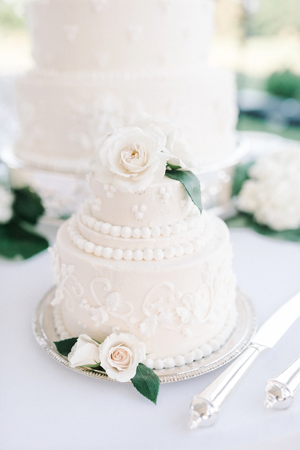 Adorable mini version of larger white wedding cake with sugar flowers