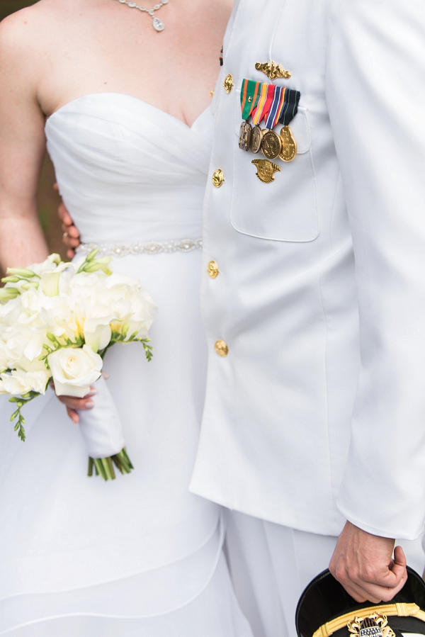Groom in uniform and bride with all white wedding bouquet