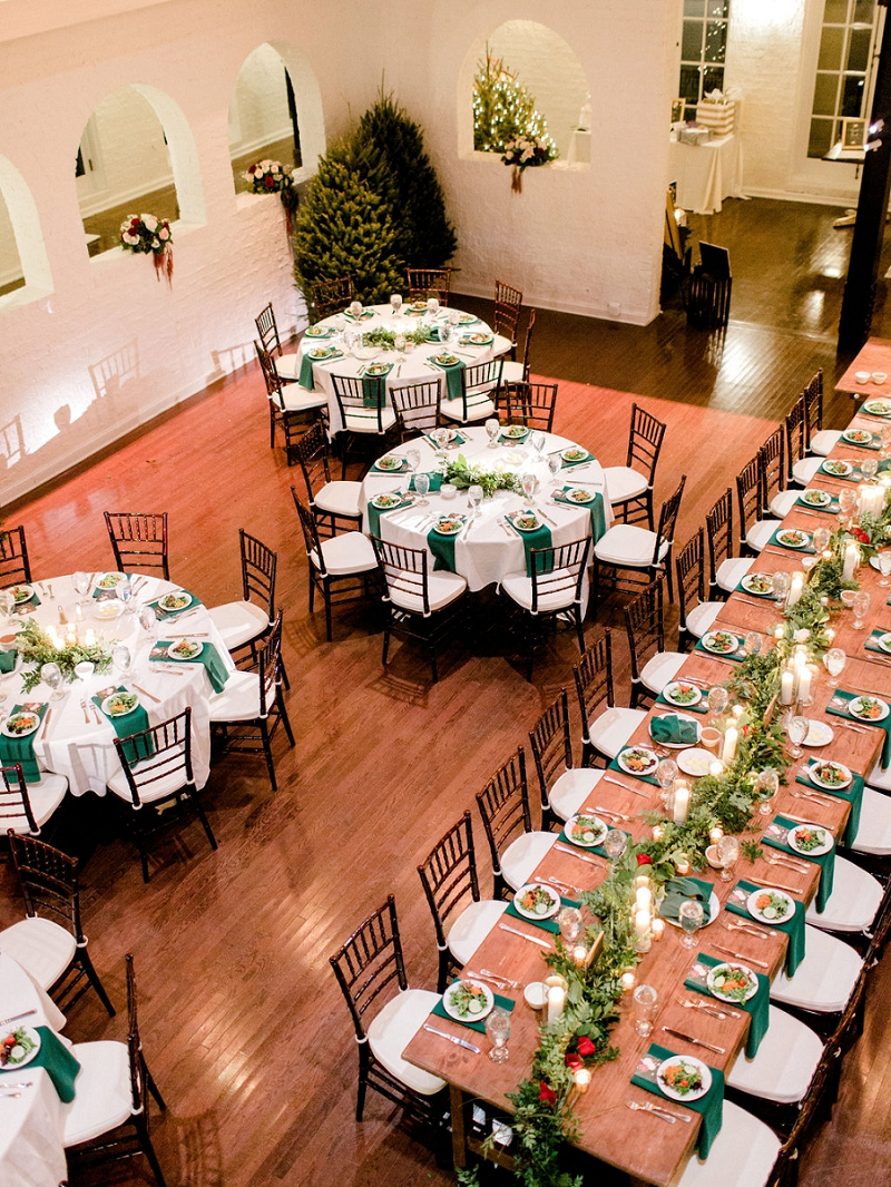 Rustic and cozy indoor wedding reception with evergreen trees inspired by the winter holidays
