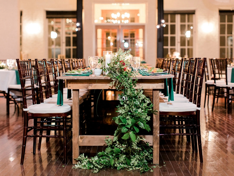 Farm tables and overflowing greenery table runner for indoor Christmas wedding