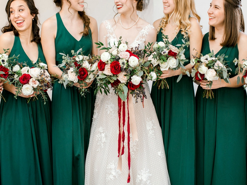 Emerald green bridesmaid dresses and red bouquets for Christmas inspired wedding