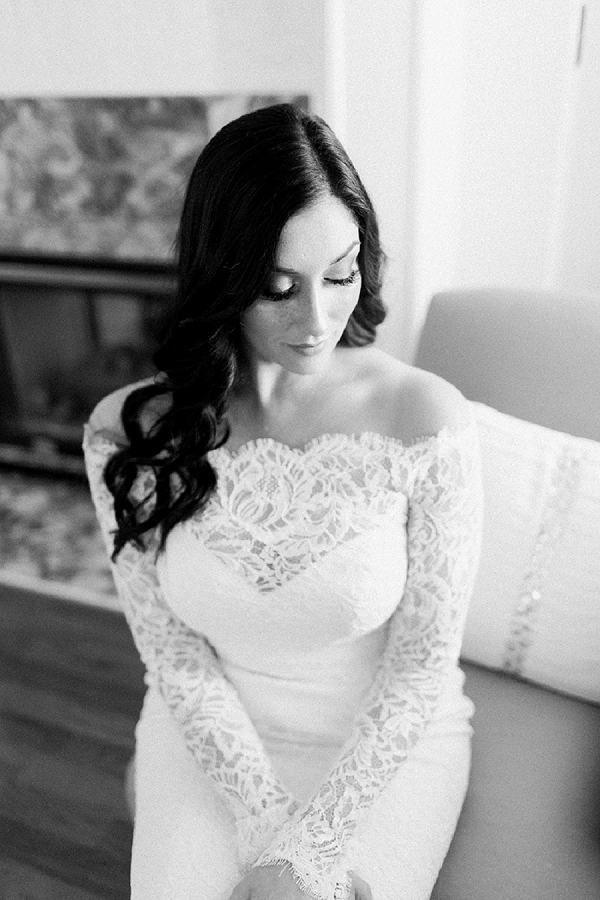 Timeless black and white portrait of boho bride wearing long lace sleeves on her wedding dress