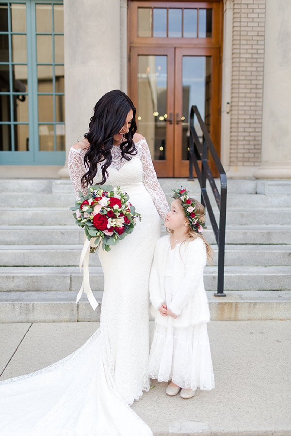 Adorable bride and flower girl with matching red and white flowers
