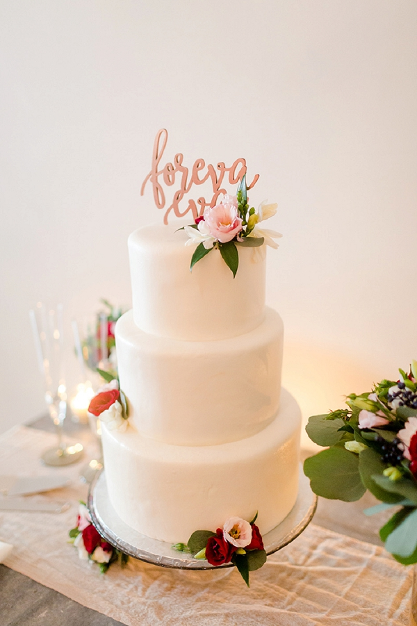 Tiered white wedding cake with Forever Eva rose gold cake topper