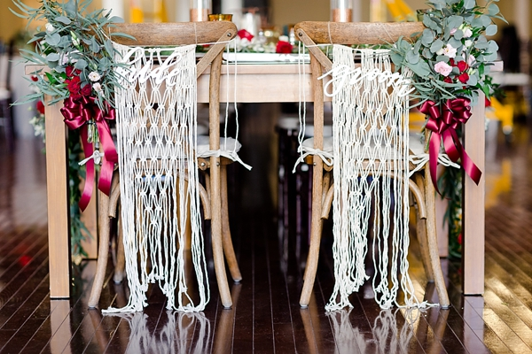 Modern boho sweetheart wedding chairs with macrame swag and red ribbon