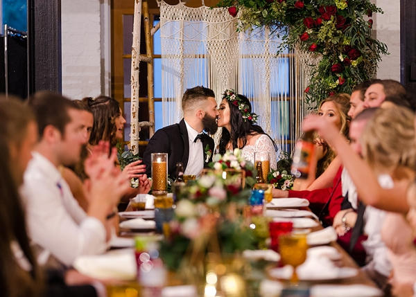 Romantic wedding moment with macrame backdrop and floral swag with roses and eucalyptus