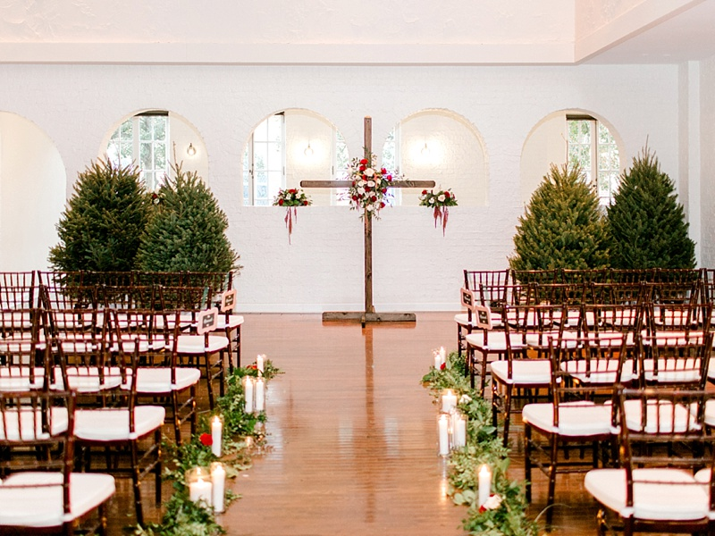Christmas trees and Christian cross decorated with florals for winter holiday wedding ceremony at The Historic Post Office in Hampton