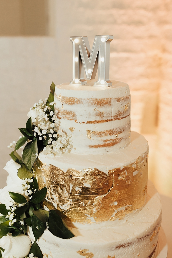 Tiered gold wedding cake with semi naked layers and industrial monogram cake topper