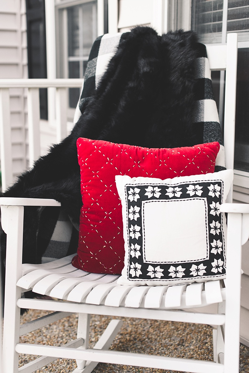 Black and white buffalo check blanket with a red velvet pillow and a Nordic Star pillow