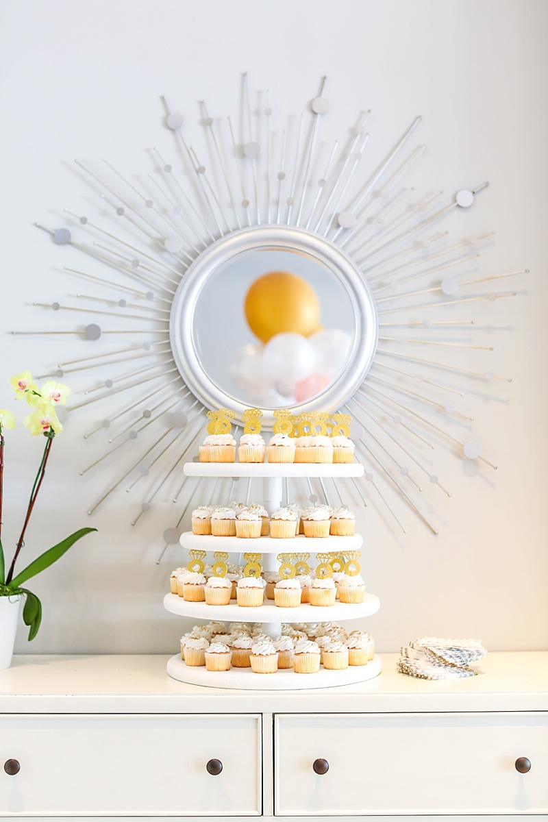 Mini white cupcake display with sparkly gold paper diamond ring cupcake toppers