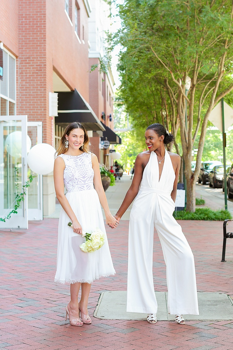 Two brides wearing a modern tea length dress and a contemporary white jumpsuit