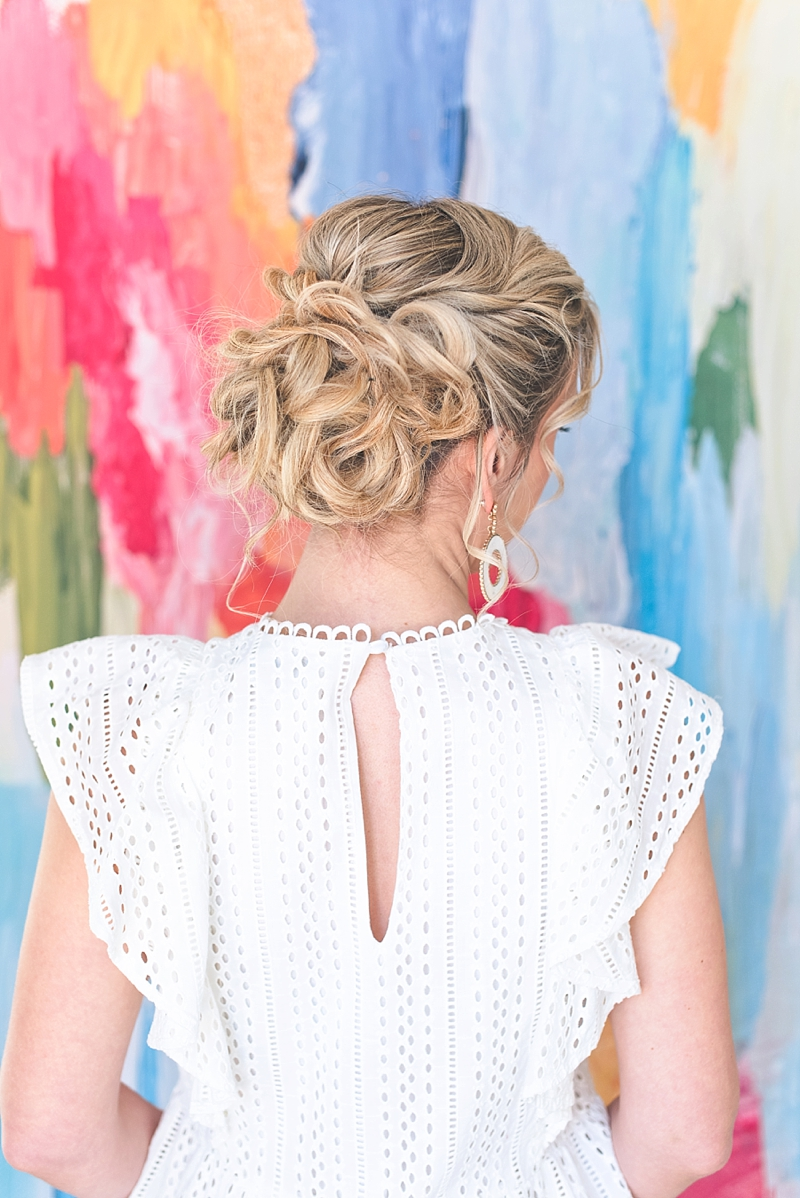 Tousled updo for boho bride with white eyelet dress