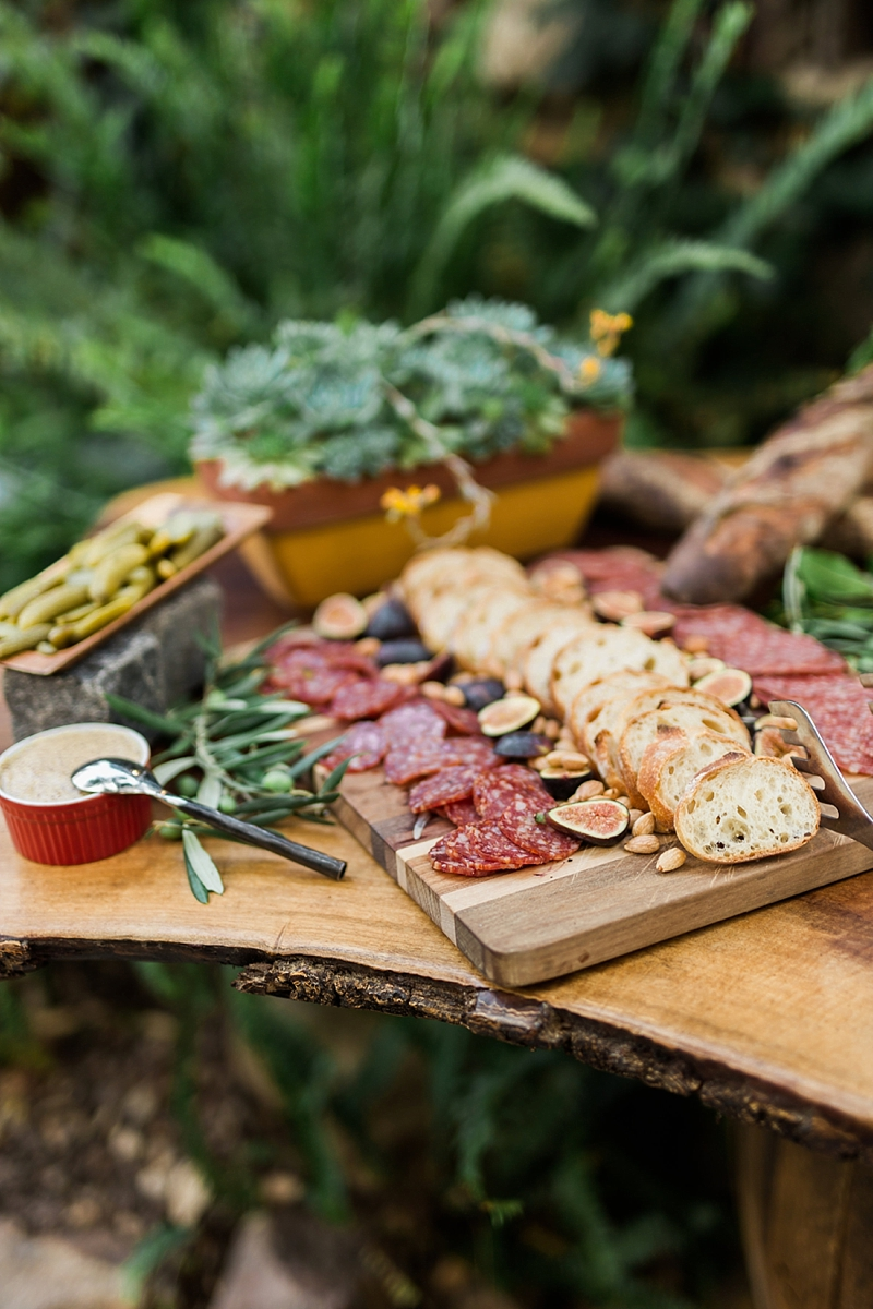 Gorgeous charcuterie on a live edge wooden slab for a chic wine country wedding
