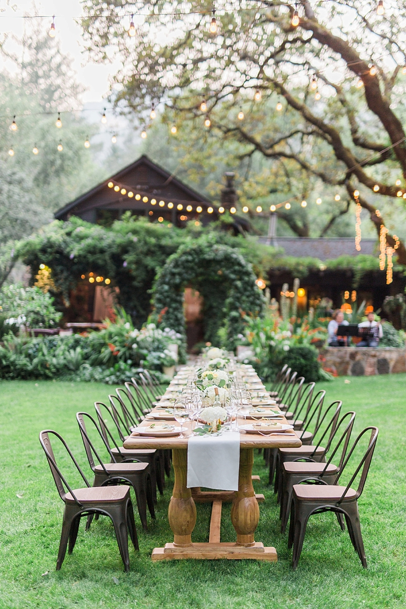Gorgeous wedding reception in the garden with bistro lights and farm tables