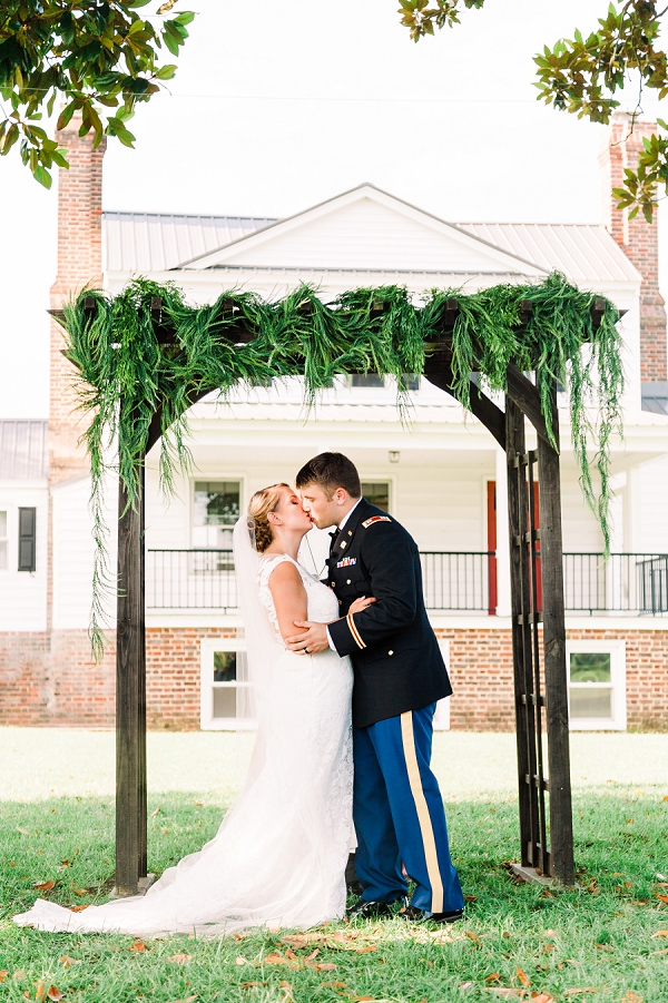 Rustic military wedding ceremony with wooden arch and overflowing greenery
