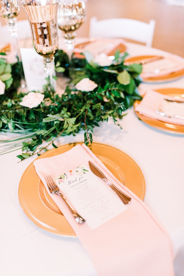 Pink napkins and romantic watercolor menu on top of gold chargers for rustic Virginia wedding