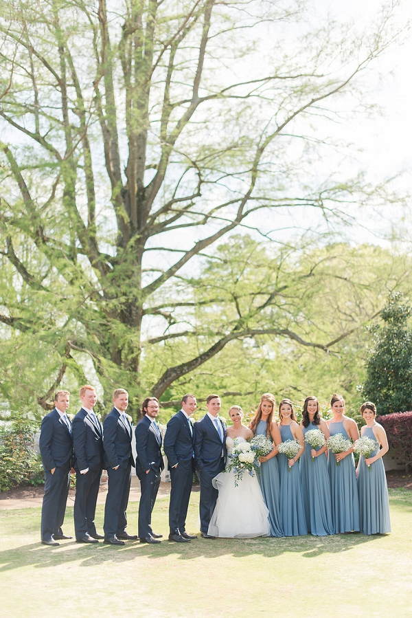 Nautical wedding party in blue bridesmaid dresses and blue groomsmen suits