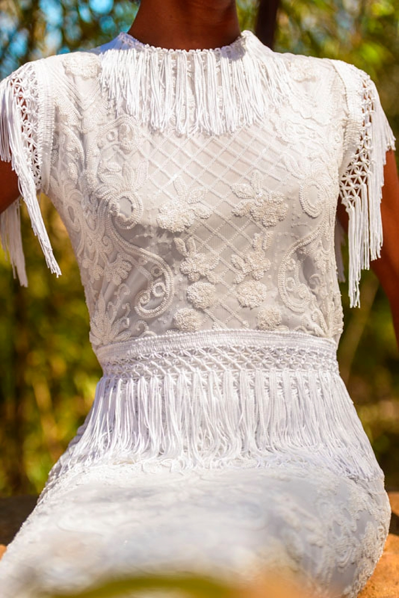 Intricately design fabric for boho wedding dress with fringed sleeves and waist