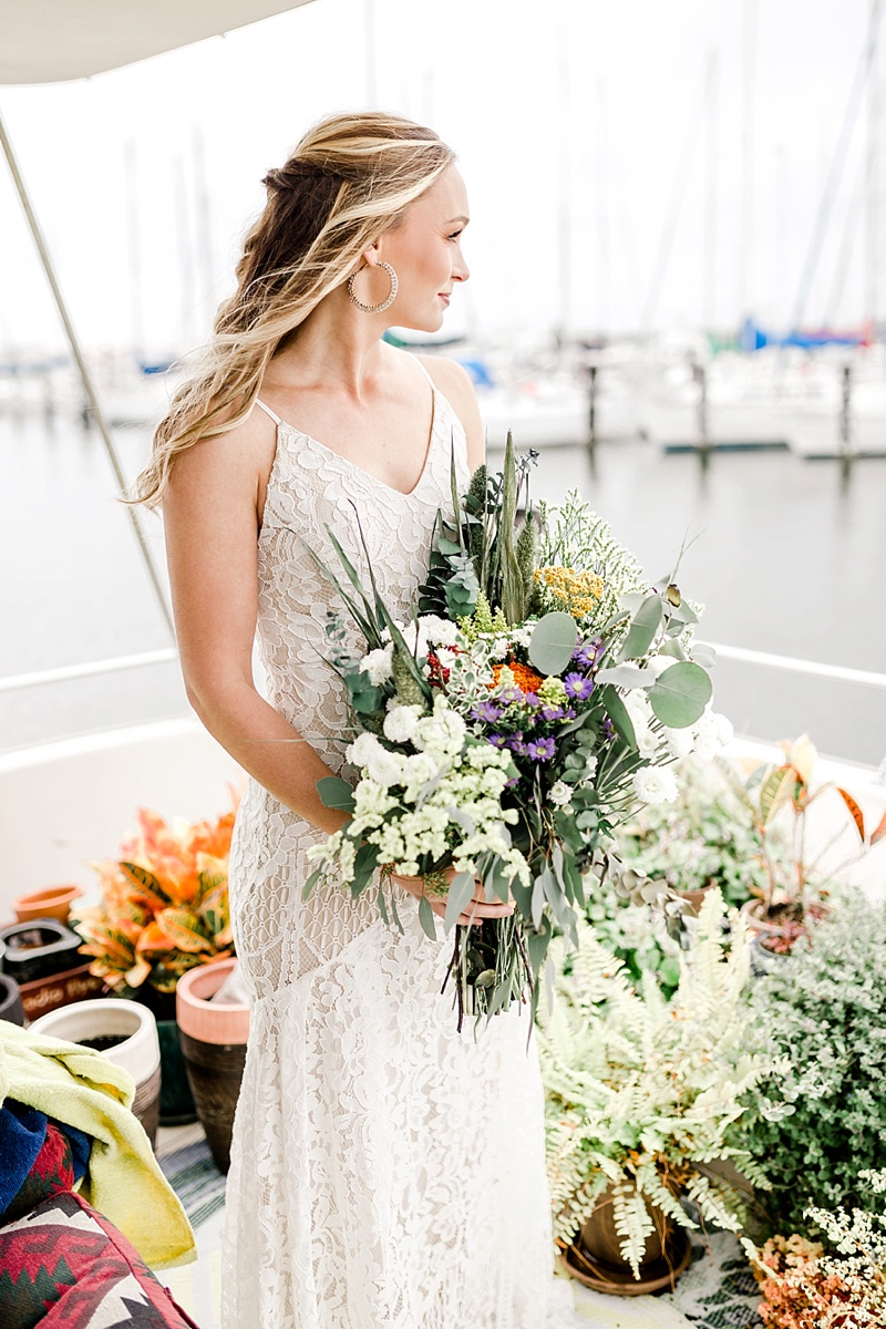 Boho bride with large gold statement hoop earrings and wildly foraged wedding bouquet