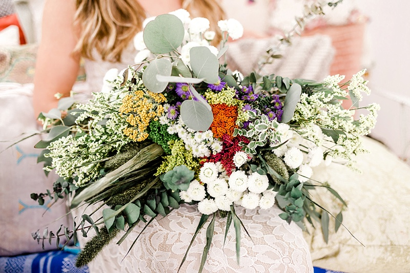 Wild and organic wedding bouquet filled with eucalyptus and tiny colorful flowers