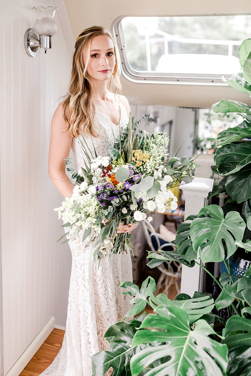 Bohemian bride surrounded by monstera plants and gorgeous colorful flowers for bridal portraits on a houseboat