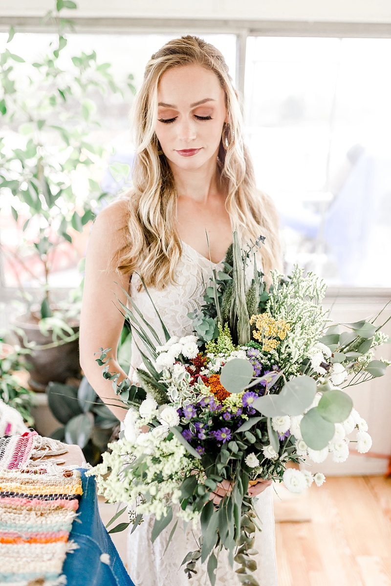 Boho bride with wildly foraged bouquet of flowers and greenery