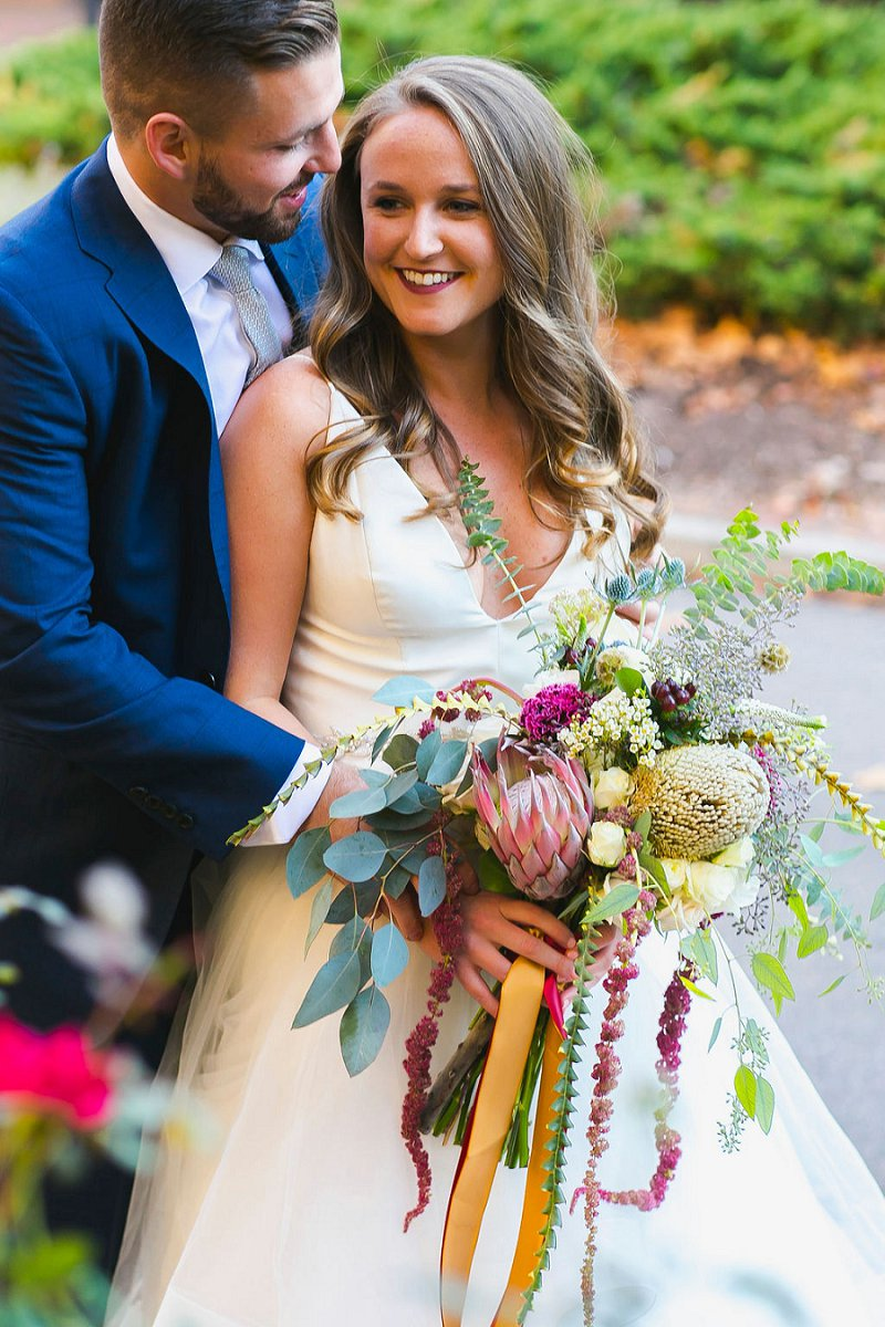 Bride and groom sharing a smile for their Norfolk Virginia boho wedding with a gorgeous colorful bouquet