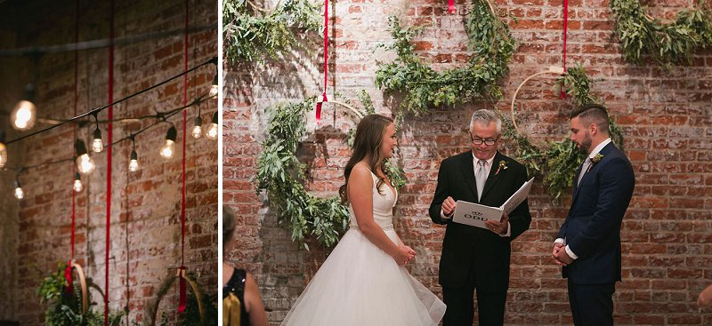 Wedding ceremony with giant gold hoops on the wall decorated with greenery
