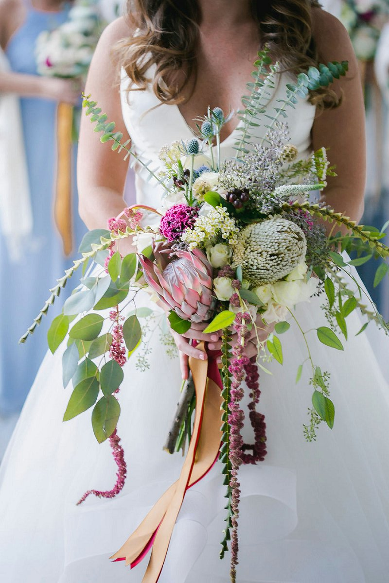 Epic wedding bouquet filled with protea and amaranthus and multi colored ribbons