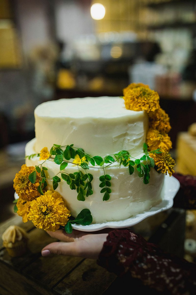 Handmade wedding cake decorated in yellow marigolds