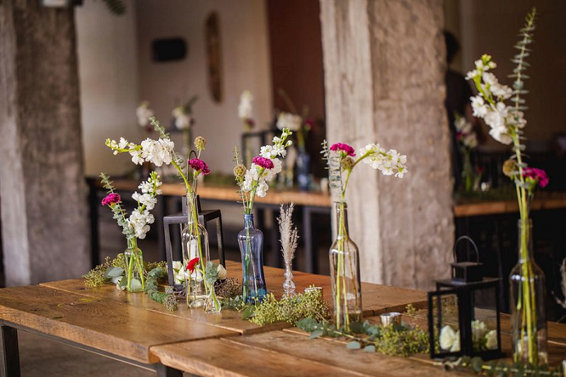 Long farm tables and colored bud vases for an indoor brick restaurant wedding in Norfolk Virginia