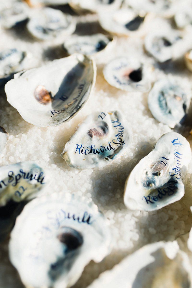 Oyster shell wedding escort cards with blue calligraphy