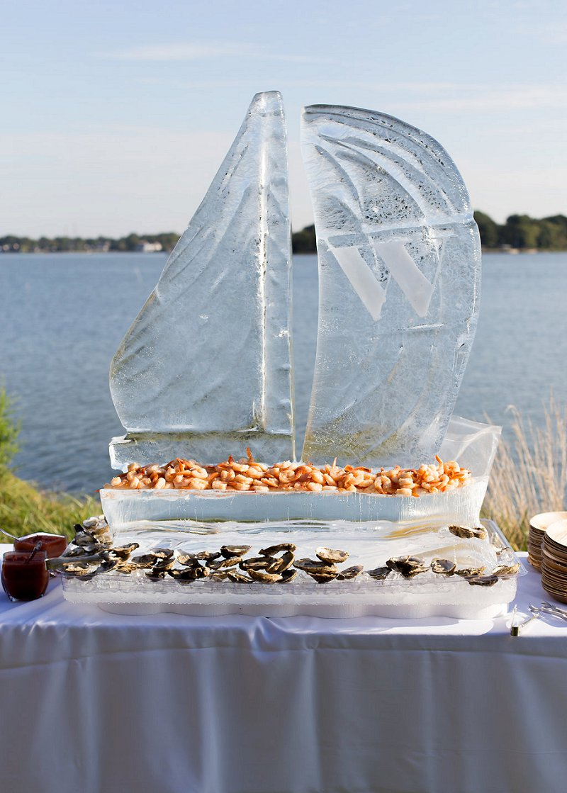 Cool ice sculpture in the shape of a sailboat for coastal wedding reception seafood bar