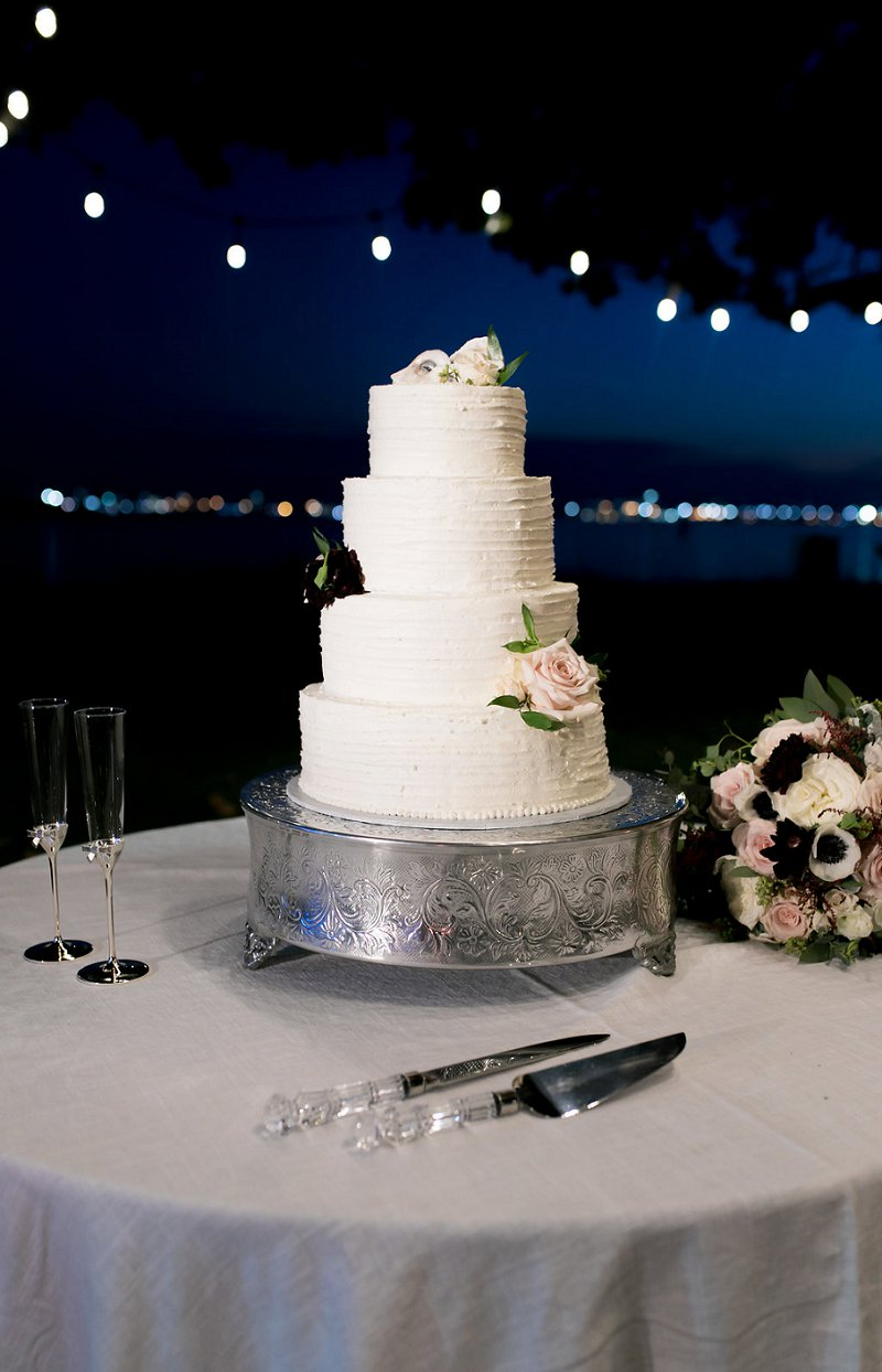 Simple white textured tiered wedding cake with oyster shells and roses for cake decor