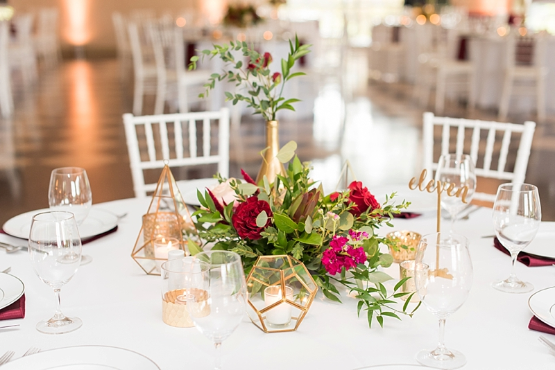 Red and gold wedding reception centerpieces with geometric glass vases with candles