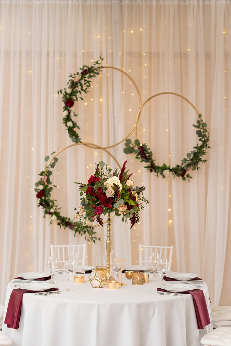 Modern wedding sweetheart table with gold hoops with floral garland on white backdrop drapery