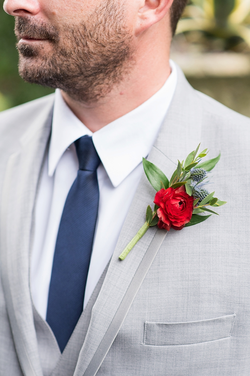 Simple red groomsman boutonniere with blue thistle and ranunculus