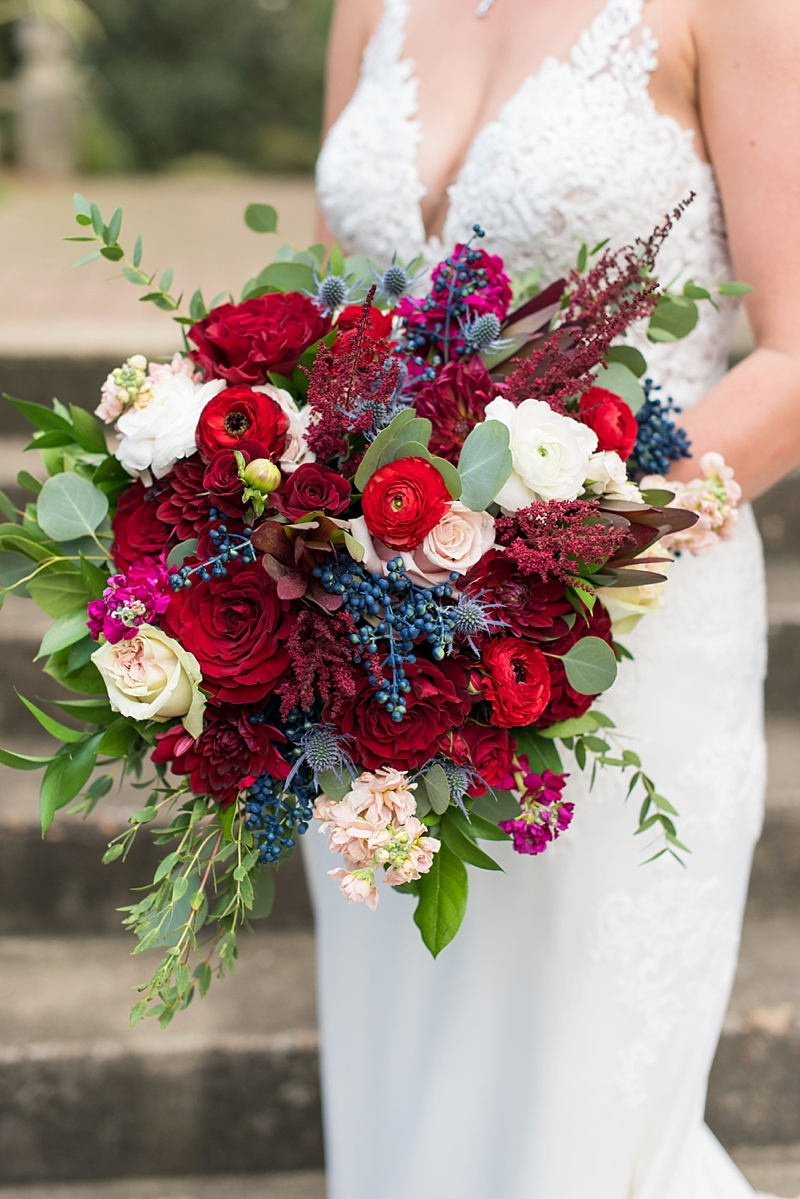 Gorgeous jewel toned wedding bouquet full of red flowers and blue berries