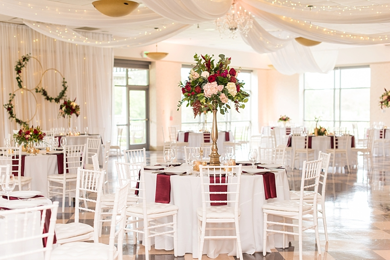 All white wedding reception with pops of red flowers and gold centerpieces and white ceiling drapery