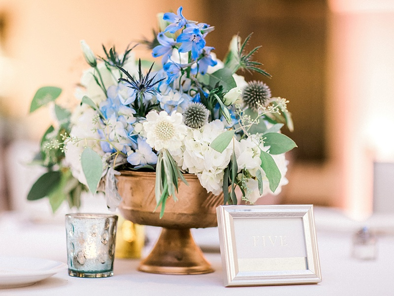Small wedding floral centerpiece in copper vase with blue and white flowers