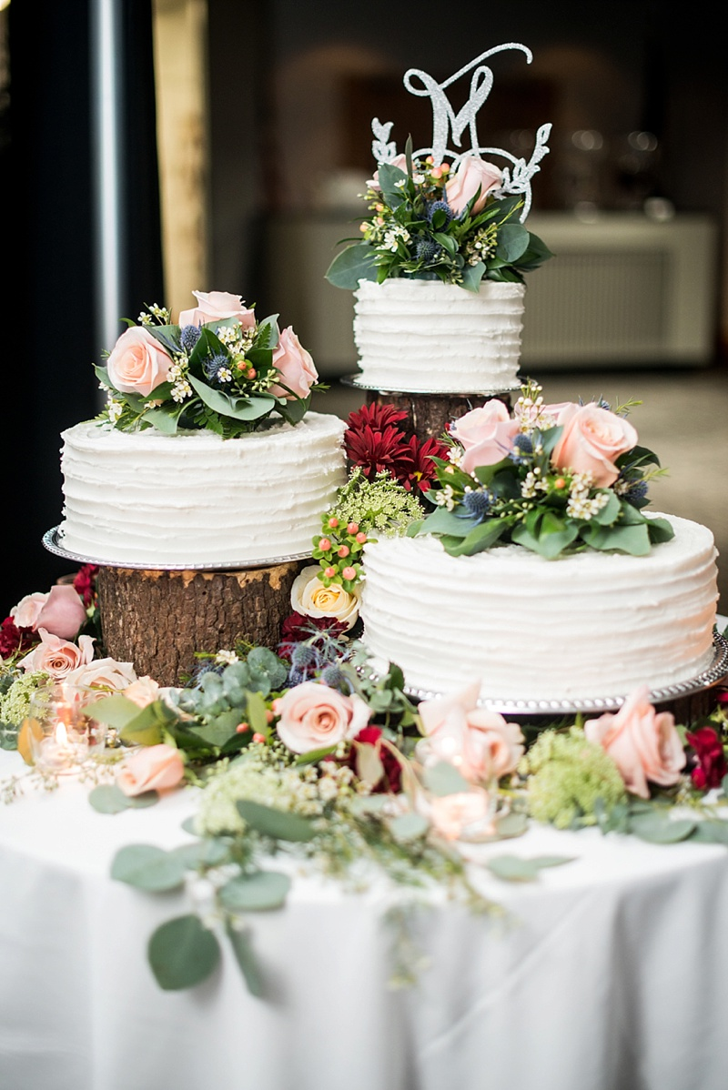 Rustic chic white textured wedding cake trio topped with roses and blue thistle flowers on top of wood logs