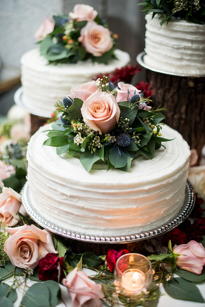 Rustic chic white textured wedding cake trio topped with roses and blue thistle flowers